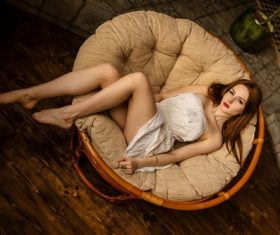 Woman lying on round sofa Stock Photo