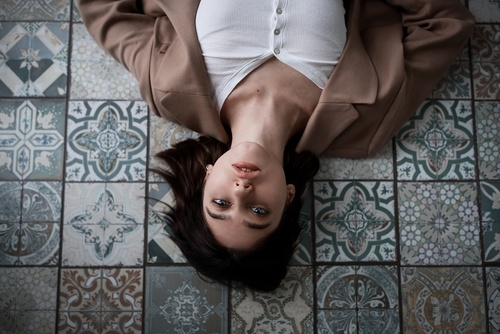 Woman lying on the floor indoors looking at the ceiling Stock Photo