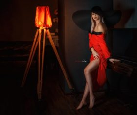 Woman posing indoors blonde hat dark red dress Stock Photo