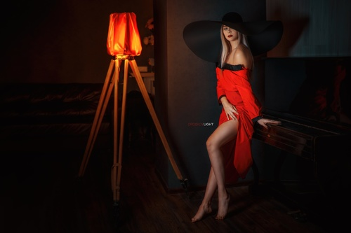 Woman posing indoors blonde hat dark red dress Stock Photo