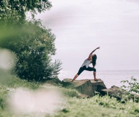 Woman practicing yoga on the rocks by the sea Stock Photo