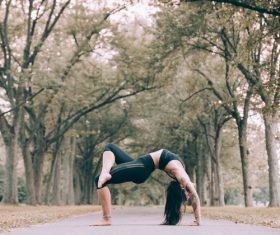 Woman practicing yoga on the tree-lined road Stock Photo