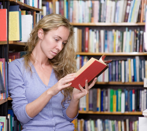 Woman reading book in the library Stock Photo