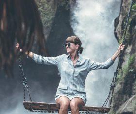 Woman swinging in scenic tourist area Stock Photo 02