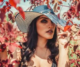 Woman wearing hat in maple woods Stock Photo