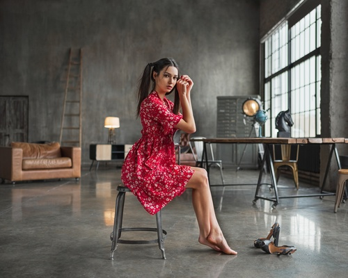 Woman wearing red floral dress doing pose on an indoor chair Stock Photo 01