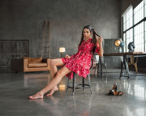 Woman wearing red floral dress doing pose on an indoor chair Stock Photo 02