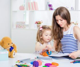 Young mother and daughter coloring picture book with colored pencils Stock Photo 06