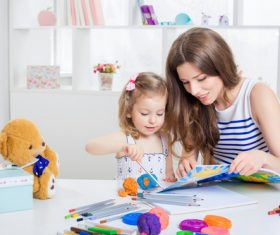 Young mother and daughter coloring picture book with colored pencils Stock Photo 05