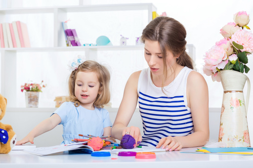 Young mother and daughter coloring picture book with colored pencils Stock Photo 04