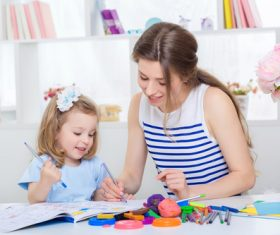 Young mother and daughter coloring picture book with colored pencils Stock Photo 03