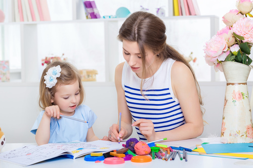Young mother and daughter coloring picture book with colored pencils Stock Photo 02