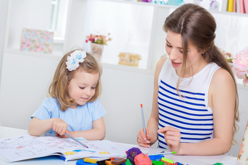 Young mother and daughter coloring picture book with colored pencils Stock Photo 01