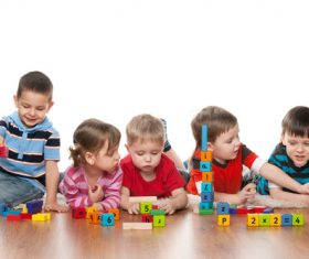 A group of children playing with building blocks Stock Photo