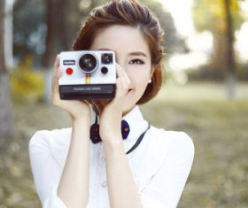 Asian woman holding camera taking photo Stock Photo