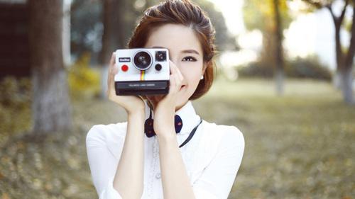 Asian woman holding camera taking photo Stock Photo
