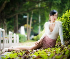 Asian woman posing in city park leaning against plants Stock Photo