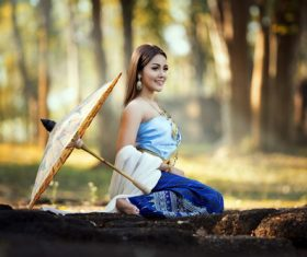 Beautiful Vietnamese woman outdoors with umbrella placed on the ground Stock Photo