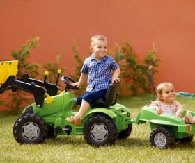 Brother driving toy car carrying sister Stock Photo