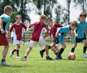 Children playing football on the grass Stock Photo