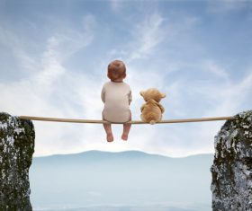 Creative photo little baby sitting on wooden bridge Stock Photo