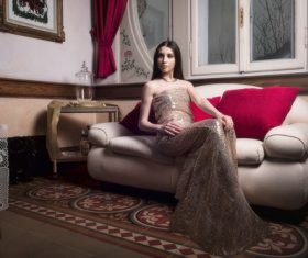 Elegant noble woman sitting on the couch Stock Photo