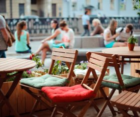 Empty tables and chairs and pedestrians Stock Photo