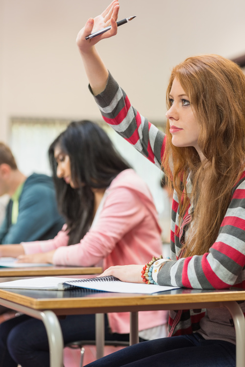 Female college student raising hand question Stock Photo