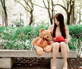 Girl and teddy bear sitting on outdoor stone bench Stock Photo