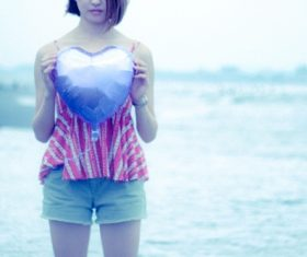 Girl holding heart shaped balloon by the sea Stock Photo