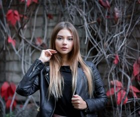 Girl in a leather jacket and red maple leaf behind her Stock Photo