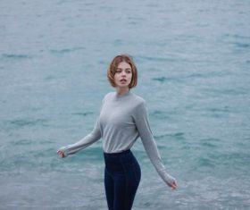 Girl in grey sweater stands by the river Stock Photo