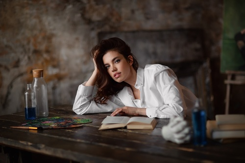 Girl leaning on the table and book on the desktop Stock Photo