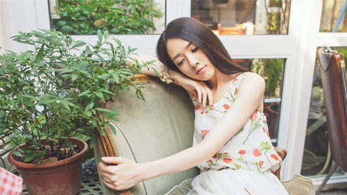 Girl sitting in a chair thinking about something Stock Photo