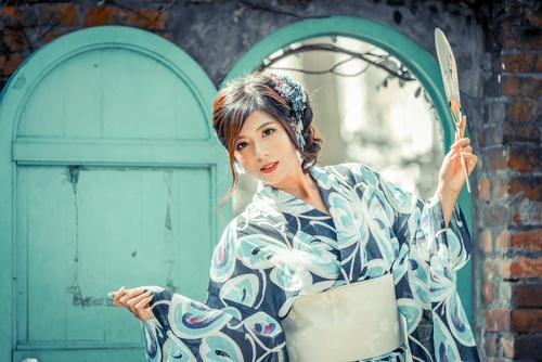 Girl wearing kimono holding fan Stock Photo