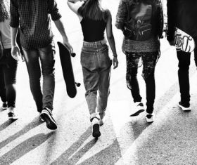 Grayscale photography of five young people walking on the road Stock Photo