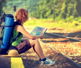 Holding map sitting on the roadside to rest backpackers Stock Photo
