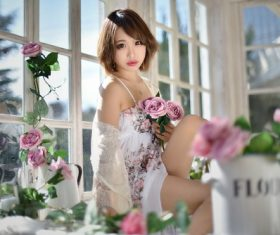 Indoor woman with flowers Stock Photo