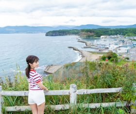 Japanese girl standing on the hillside looking at the sea Stock Photo