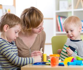 Kindergarten teacher and children Stock Photo