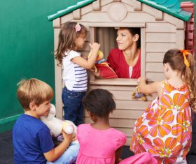 Kindergarten teacher interacts with children Stock Photo