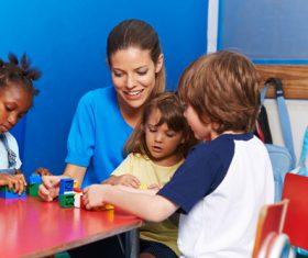 Kindergarten teacher playing with children Stock Photo 01