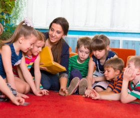 Kindergarten teacher tells stories to children Stock Photo