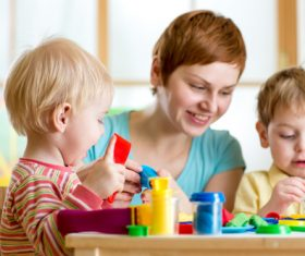 Kindergarten teacher watching children do manual Stock Photo