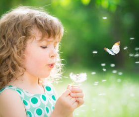 Little girl blowing dandelion flower Stock Photo