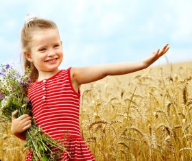 Little girl holding bouquet in wheat field Stock Photo