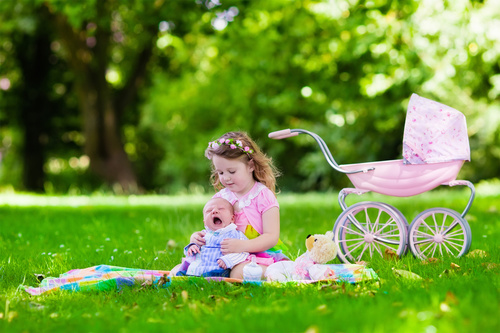 Little girl playing with newborn baby brother in summer park Stock Photo 01