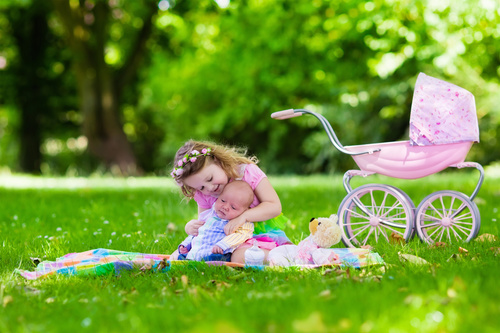 Little girl playing with newborn baby brother in summer park Stock Photo 02