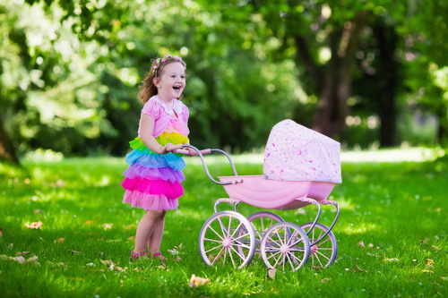 Little girl playing with newborn baby brother in summer park Stock Photo 03