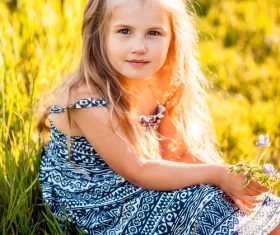 Little girl sitting on the grass Stock Photo